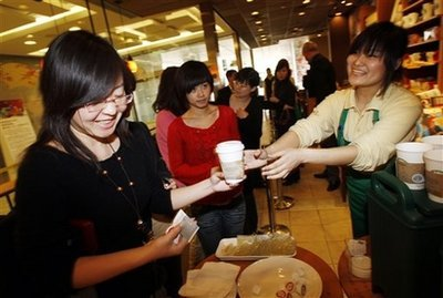 A Starbucks staff member hands out free coffee to customers at an event to mark the 10th anniversary of Starbucks' launch in China, at the the company's original outlet in Beijing Wednesday, Jan. 14, 2009. The Coffee chain Starbucks has started producing coffee grown by farmers in China and hopes to bring the blend to stores all over the world. (AP Photo/Greg Baker)