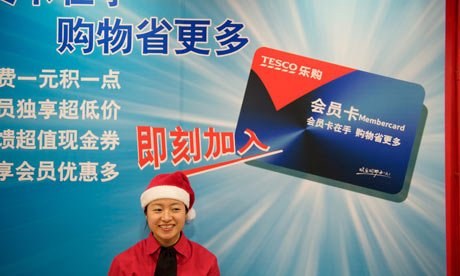 chinese tesco employee standing in front of club card display in china